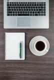 膝上型计算机、笔记本和咖啡杯在工作书桌上 免版税库存图片