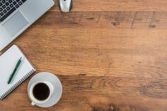 膝上型计算机、笔记本和咖啡杯在工作书桌上 库存图片