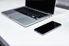 膝上型计算机、笔记本和电话,在桌上的智能手机 办公桌t 免版税库存图片