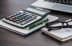膝上型计算机、笔记本和笔与计算器在书桌上 免版税库存图片