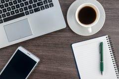 膝上型计算机、笔记本片剂和咖啡杯在工作书桌上 免版税图库摄影
