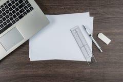 膝上型计算机、纸笔统治者和橡皮擦在工作书桌上 免版税库存图片