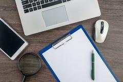 膝上型计算机、老鼠、扩大化的纸和笔与片剂 免版税库存照片