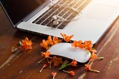 膝上型计算机、耳机和花在木桌背景 库存图片