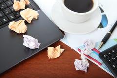 膝上型计算机、计算器、咖啡和被弄皱的纸 库存照片