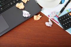 膝上型计算机、计算器、咖啡和被弄皱的纸 免版税库存照片