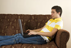 膝上型计算机人坐沙发运作的年轻人 免版税图库摄影