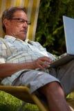 膝上型计算机人室外前辈使用 免版税库存照片