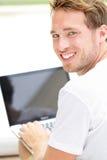 膝上型计算机人微笑愉快使用计算机外面 图库摄影