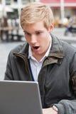 膝上型计算机人震惊年轻人 图库摄影