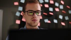 膝上型计算机人 玻璃工作的年轻人在一台膝上型计算机在办公室 商人-办公室工作者 男生工作 股票录像