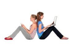 膝上型计算机使用妇女的MP3播放器 免版税库存图片