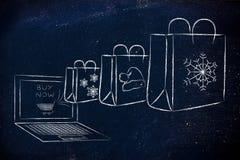 从膝上型计算机出来的圣诞节主题的购物袋 库存照片