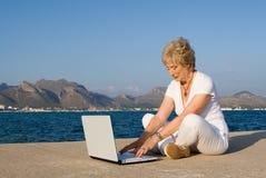 膝上型计算机前辈妇女 库存图片