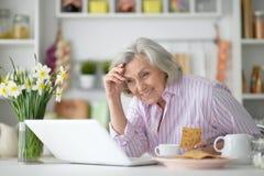 膝上型计算机前辈妇女 图库摄影