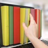 膝上型计算机和五颜六色的书。 免版税库存图片