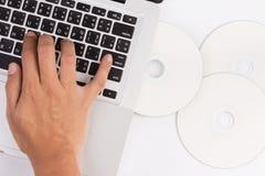 膝上型计算机和光盘用手 库存图片