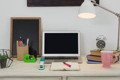 膝上型计算机和各种各样的办公室辅助部件在桌上 图库摄影