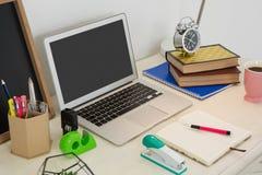 膝上型计算机和各种各样的办公室辅助部件在桌上 免版税库存图片