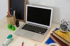 膝上型计算机和各种各样的办公室辅助部件在桌上 免版税库存照片