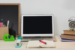膝上型计算机和各种各样的办公室辅助部件在桌上 库存照片