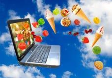 膝上型计算机和各种各样的甜点在天空背景 免版税图库摄影