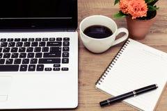 膝上型计算机和咖啡与花的在书桌上 库存图片