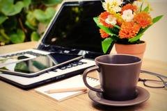 膝上型计算机和咖啡与花的在书桌上 免版税库存照片