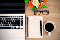 膝上型计算机和咖啡与花的在书桌上 免版税库存图片