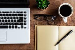 膝上型计算机和咖啡在老木桌上的 免版税库存图片