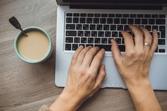 膝上型计算机和咖啡杯在女孩的手上坐一木backgr 免版税图库摄影