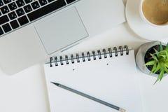 膝上型计算机和咖啡顶视图有办公用品的在台式的 库存图片