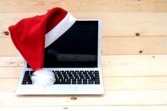 膝上型计算机和圣诞老人帽子 库存照片