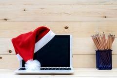 膝上型计算机和圣诞老人帽子 免版税库存照片