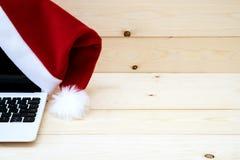 膝上型计算机和圣诞老人Slaus帽子 免版税图库摄影