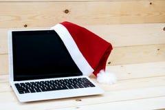 膝上型计算机和圣诞老人Slaus帽子 图库摄影