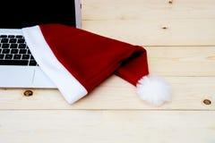 膝上型计算机和圣诞老人Slaus帽子 免版税库存照片