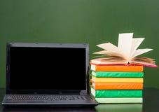 膝上型计算机和堆书临近空的绿色黑板 文本的样品 免版税库存图片
