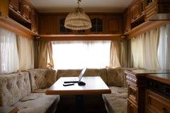 膝上型计算机和智能手机在一张桌上在一个小舒适厨房,一个共同的计划里 免版税库存图片