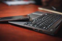 膝上型计算机和智能手机在办公室桌上 免版税库存照片