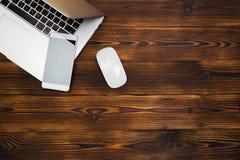 膝上型计算机和智能手机在木背景顶视图 免版税库存照片