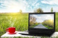 膝上型计算机和杯子在桌上的热的咖啡,室外办公室 汽车城市概念都伯林映射小的旅行 企业想法 其余nat 免版税库存图片
