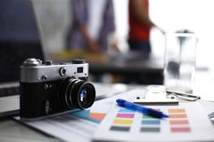 膝上型计算机和照相机在书桌上,站立在背景中的两买卖人 图库摄影