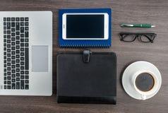膝上型计算机和片剂有笔记本的和笔在书桌上 免版税库存照片