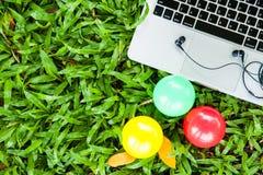 膝上型计算机和球在草 免版税图库摄影