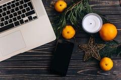 膝上型计算机和电话有空的屏幕的圣诞节季节性广告的 图库摄影