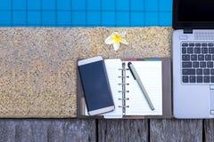 膝上型计算机和空的笔记本在游泳池边缘 免版税库存照片
