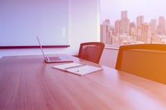 膝上型计算机和笔在笔记薄议程的在桌上保留在空的公司会议室有都市风景视图在背景 免版税库存图片