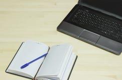 膝上型计算机和笔记本有笔的在木书桌上 库存照片