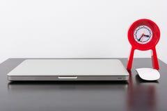 膝上型计算机和红色时钟在黑木桌上 免版税图库摄影